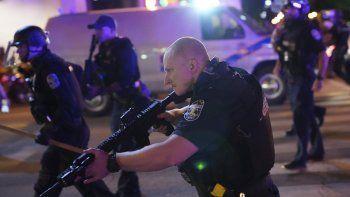 Policías avanzan después de que un agente de Louisville resultara baleado el miércoles 23 de septiembre de 2020, durante protestas contra la injusticia racial en Louisville, Kentucky.