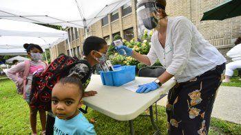 Ruth Venman-Clay, para-educadora en la Escuela Primaria Greenstreet, en Brattleboro, Vermont, le toma la temperatura a niños en el primer día del año escolar.