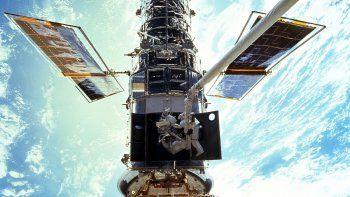 En esta imagen provista por NASA/JSC, los astronautas Steven L. Smith y John M. Grunsfeld realizan trabajos de mantenimiento del Telescopio Espacial Hubble en diciembre de 1999. El Hubble estará funcionando de nuevo pronto, luego de una difícil reparación remota por la NASA, se anunció el 16 de julio del 2021.