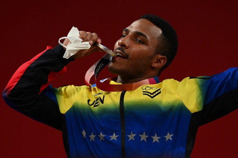 El venezolano Julio Rubén Mayora Pernia posa con su medalla de plata en el podio de la ceremonia de victoria de la competencia de halterofilia masculina de 73 kg durante los Juegos Olímpicos de Tokio 2020