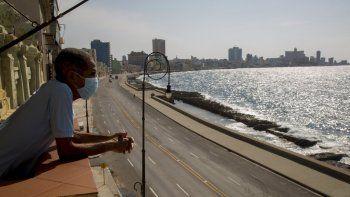 El trabajador Julio Diago mira la carretera vacía a lo largo del malecón desde el restaurante Nazdarovie, que está cerrado por la cuarentena para contener la propagación del nuevo coronavirus en La Habana, Cuba, el lunes 27 de abril de 2020.