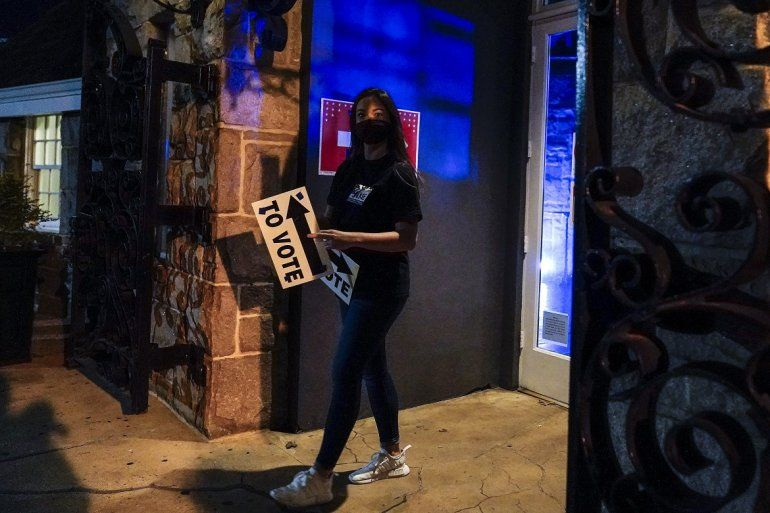 Una trabajadora electoral sale de un centro de votación con un cartel que indica la entrada a las urnas antes de su apertura el martes 3 de noviembre del 2020