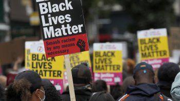 En imagen de archivo del domingo 230 de agosto de 2020, manifestantes del movimiento Black Lives Matter sostiene carteles durante la Marcha del Millón de Personas por el centro de Londres.