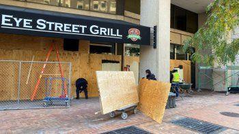 Trabajadores colocaron madera alrededor de edificios para protegerse de posibles disturbios civiles durante la carrera presidencial de Estados Unidos por la Casa Blanca en Washington, DC.
