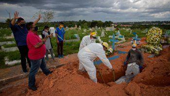 Familiares rezan durante el funeral de la víctima de COVID-19 Paulo Ferreira Campos, de 57 años, en el cementerio de Nossa Senhora Aparecida en Manaus, estado de Amazonas, Brasil, el 15 de abril de 2021. Covid-19 ha cobrado más de 3,000 vidas por día en promedio en Brasil durante la semana pasada, la mayor cantidad en todo el mundo. El país de 212 millones de personas tiene un número total de muertos de más de 360.000, solo superado por Estados Unidos