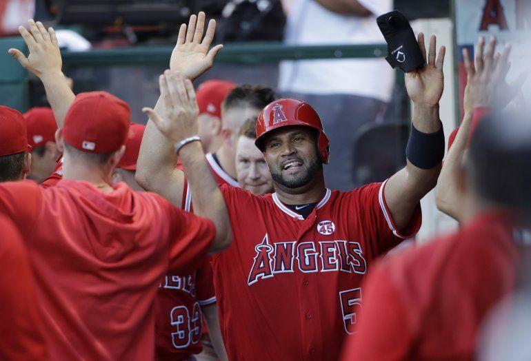 El jugador de los Angelinos de Los Ángeles Albert Pujols (centro) recibe la felicitación de sus compañeros tras anotar