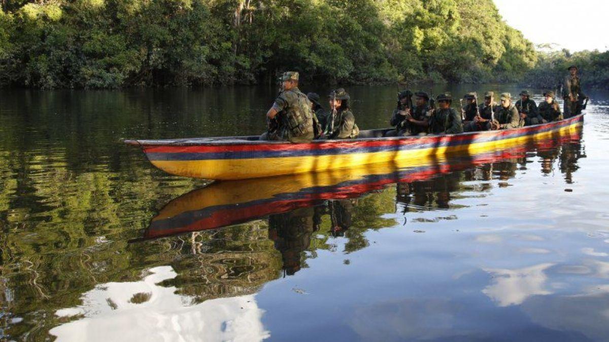 Guerrilleros navegan un río entre Colombia y Venezuela.