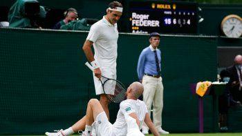 Roger Federer charla con Adrian Mannarino tras la lesión sufrida por este en el duelo de primera ronda del torneo de Wimbledon, el martes 29 de junio de 2021, en Londres