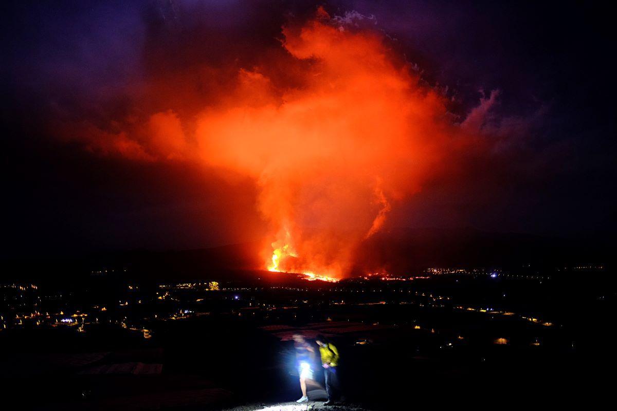 Dos personas caminan durante la noche mientras un volcán expulsa lava, en La Palma, Islas Canarias, el 25 de septiembre de 2021.