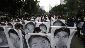 Estudiantes normalistas muestran las fotografías de los 43 estudiantes desaparecidos de la Escuela Normal Rural de Ayotzinapa al acompañar a los familiares en una marcha en el sexto aniversario de la desaparición de los 43 estudiantes, en Ciudad de México, el sábado 26 de septiembre de 2020. ()