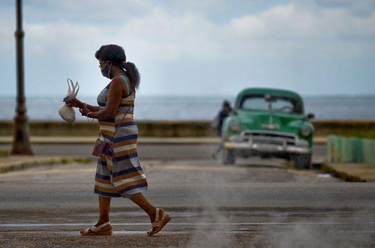 Una mujer que usa mascarilla como medida preventiva contra la pandemia del nuevo coronavirus COVID-19 camina en La Habana