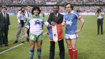 En imagen de archivo del 23 de mayo de 1998, el astro argentino Diego Armando Maradona, izquierda, el brasileño Pelé, centro, y el francés Michel Platini posan estrechando manos durante el partido de despedida de Platini en el estadio Nancy, en el este de Francia.