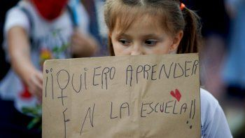 Una niña sostiene un cartel durante una protesta afuera del Ministerio de Educación luego de que el gobierno de Argentina decidió suspender las clases presenciales para frenar un aumento de casos de coronavirus en Buenos Aires, el viernes 16 de abril de 2021.