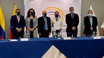 El expresidente Andrés Pastrana, luego de su lectura, entrega a Diana Atamaint, presidenta del Consejo Nacional Electoral de Ecuador la declaración de IDEA sobre el proceso electoral celebrado en Ecuador.