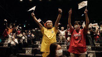 La gente reacciona después de que el equipo de softbol de Japón ganó la medalla de oro en su partido contra Estados Unidos durante los Juegos Olímpicos de Tokio 2020 mientras ven el partido en el Teatro de la Ciudad de Takasaki en Takasaki