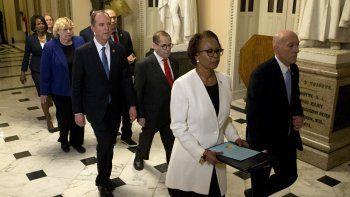 El sargento de armas de la Cámara de Representantes, Paul Irving, y la oficial mayor de la cámara baja Cheryl Johnson llevan los cargos de juicio político contra el presidente Donald Trump hacia el Senado el miércoles 15 de enero de 2015 en el Capitolio de Washington.
