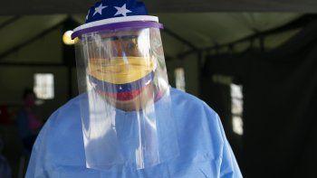 Con una mascarilla decorada con los colores de la bandera venezolana y una careta, la directora de hospital, doctora Zaira Medina, está parada en una carpa montada a la entrada del hospital Ana Francisca Pérez de León mientras supervisa la aplicación de las pruebas rápidas para coronavirus en Caracas, Venezuela, el miércoles 15 de abril de 2020.