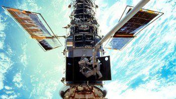 En esta imagen provista por NASA/JSC, los astronautas Steven L. Smith y John M. Grunsfeld realizan mantenimiento al Telescopio Espacial Hubble en diciembre de 1999.