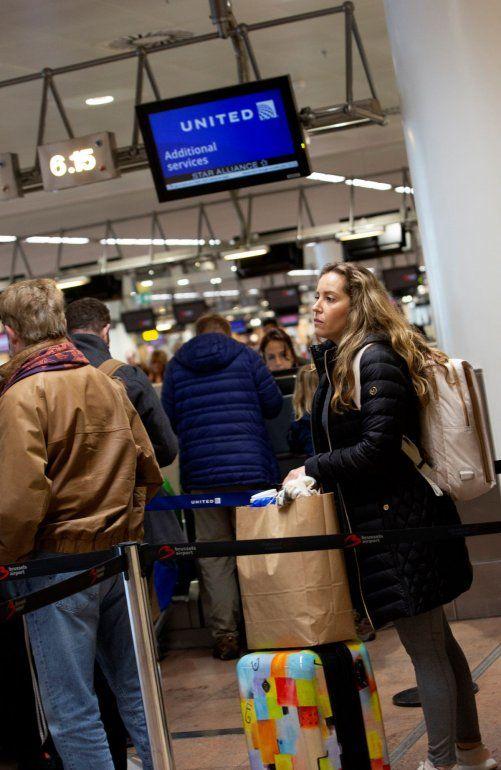 La estadounidense Christine Barto hace fila para preguntarle sobre su vuelo a un representante en un mostrador de United Airlines en el aeropuerto internacional de Bruselas