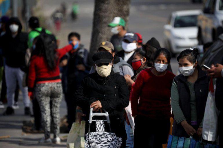 Personas hacen cola para recibir un plato de comida en un comedor de beneficencia durante un confinamiento ordenado por el gobierno para frenar la propagación del coronavirus en Buenos Aires