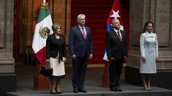 El presidente mexicano Andrés Manuel López Obradory su esposa Beatriz Gutiérrez, derecha, yel designado gobernante cubano Miguel Díaz-Canel con su esposa Lis Cuesta, izquierda, escuchan los himnos nacionales durante una ceremonia de bienvenida en Palacio Nacional en Ciudad de México el jueves 17 de octubre de 2019.
