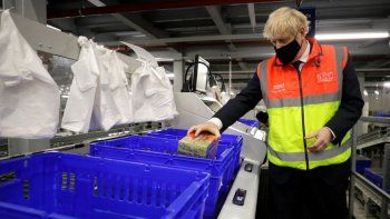 El primer ministro británico Boris Johnson coloca alimentos en canastas de plástico el miércoles 11 de noviembre de 2020 durante una visita a un centro de distribución en línea de los supermercados Tesco, en Londres.