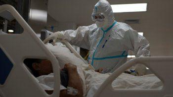 Un trabajador sanitario español y voluntario de la Fundación SAMU atiende a un paciente salvadoreño que sufre una crisis respiratoria por el nuevo coronavirus, COVID-19, en la unidad de cuidados intensivos del Hospital El Salvador, en San Salvador, el 12 de agosto de 2020.