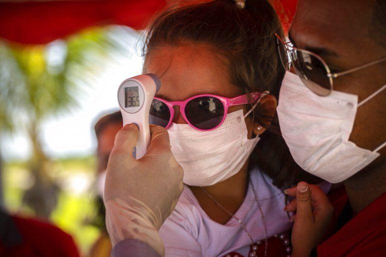 A una niña con mascarilla para protegerse del nuevo coronavirus le toman la temperatura en un puesto de control policial en la entrada de la provincia de La Habana