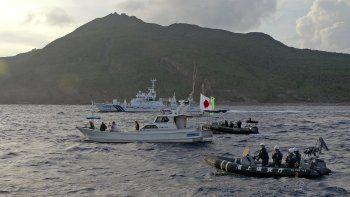 Un barco de la Guardia Costera de Japón navega cerca de otros barcos advirtiendo que se alejen de un grupo de islas en disputa por Japón y China, el 18 de agosto de 2013.
