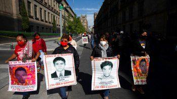 Mujeres con fotografías de sus familiares desaparecidos, que se encuentran entre los 43 estudiantes desaparecidos en Ayotzinapa, México,caminan hacia la puerta del Palacio Nacional donde se reunirán con el presidente Andrés Manuel López Obrador.