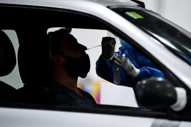 Un trabajador de salud recolecta muestras para la prueba de detección de casos de coronavirus COVID-19 dentro de un automóvil