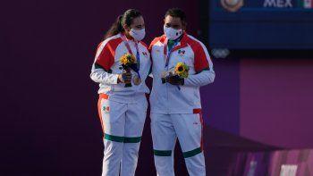 Los mexicanos Alejandra Valencia (izquierda) y Luis Álvarez celebran en el podio tras conseguir una medalla de bronce en la prueba mixta del tiro con arco de los Juegos Olímpicos de Tokio