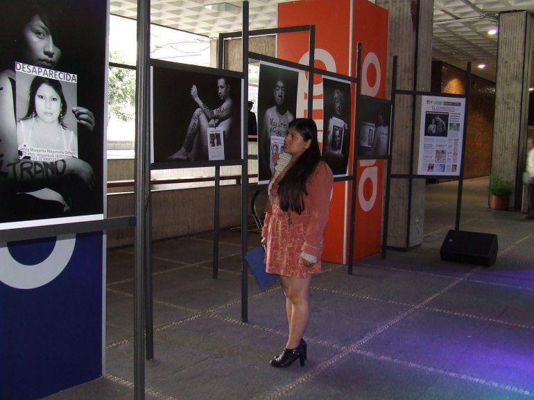 Una mujer observa fotografías tomadas por Paul Rivas