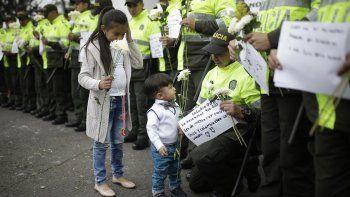 Niños reciben flores de parte de integrantes de la Policía deColombiadurante un homenaje a los cadetes muertos por la explosión del carro bomba contra la Escuela de la Policía General Santander.