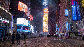 Un Times Square casi vacío, en la parte superior, en las primeras horas del viernes 1 de enero de 2021 en Nueva York y el mismo lugar tomado el 1 de enero de 2020 lleno de juerguistas que celebran el Año Nuevo.