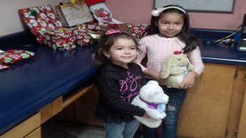 Dayami de 8 años, junto a su hermana Ximena de 4, años sosteniendo en la cocina de su casa en México los regalos que les trajo de Estados UnidosRandyHeiss.