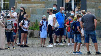 Fotografía de archivo del miércoles 12 de agosto de 2020 de padres esperando con sus hijos en el patio escolar para el primer día de clases en Gelsenkirchen, Alemania.
