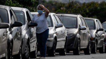 Un conductor reacciona mientras espera en una cola para repostar el tanque de gasolina de su automóvil cerca de una estación de servicio en Caracas el 7 de abril de 2020 en medio del nuevo brote de coronavirus (COVID-19).
