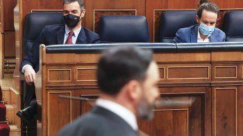 El líder de VOX, Santiago Abascal, pasa frente al presidente del Gobierno, Pedro Sánchez (i) y el vicepresidente segundo, Pablo Iglesias (d), en el pleno del Congreso.