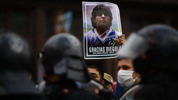 Un hombre sostiene un póster con la cara de Diego Maradona mientras espera en el exterior de la Casa Rosada para acceder a la capilla ardiente, en Buenos Aires, Argentina, el 26 de noviembre de 2020.