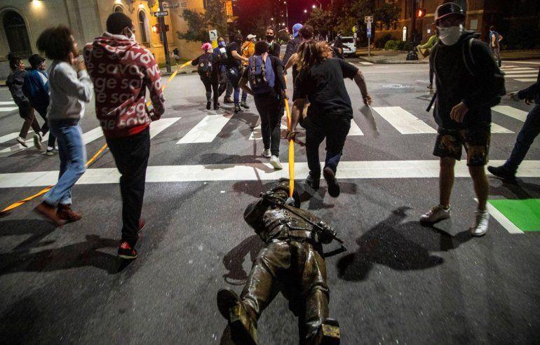 Varios manifestantes arrastran una estatua tomada del monumento a la Confederación en el Capitolio del estado en Raleigh