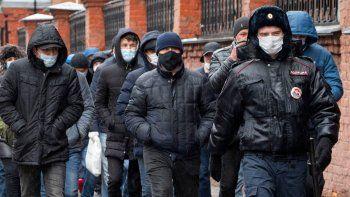 ARCHIVO - En esta fotografía del 2 de abril de 2020, unos agentes de la policía acompañan a un grupo de migrantes, en San Petersburgo, Rusia. La ONU había proyectado que la migración internacional crecería entre 7 y 8 millones para mediados de 2019 y mediados de 2020.