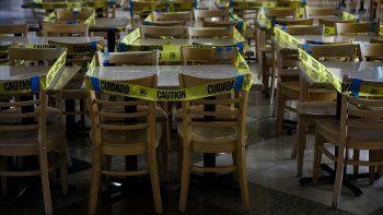 Un precinto de cinta amarilla rodea mesas y sillas en una zona de restaurantes para evitar que se usen los comedores interiores durante la pandemia del coronavirus, en Koreatown, Los Ángeles, el 8 de julio de 2020.