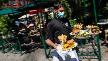 Un camarero con una mascarilla para protegerse del coronavirus entrega comida en la sección al aire libre de un restaurante, el viernes 4 de septiembre del 2020, en Hoboken, Nueva Jersey.