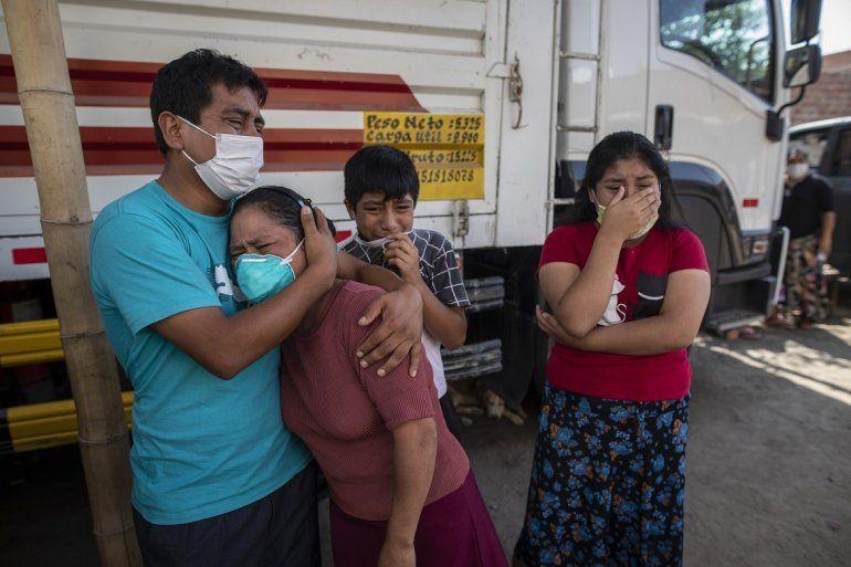 Familiares lloran mientras observan como operarios de la funeraria Piedrangel retiran el cuerpo de un pariente que se cree que murió a causa del nuevo coronavirus