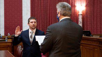 El legislador de Virginia Occidental Derrick Evans, izquierda, juramenta en la Cámara de Delegados el 14 de diciembre del 2020, en Charleston. El delegado estatal está acusado de ingresar a un área restringida del Capitolio estadounidense.