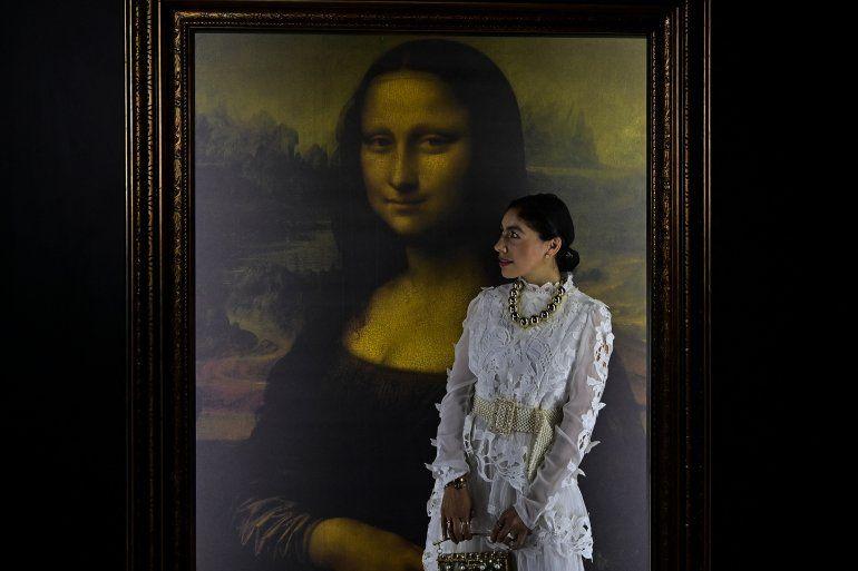 Una mujer posa para fotografías junto a una reproducción del retrato de Lisa Gherardini