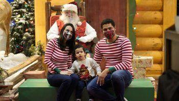 Ariadna y Brian Ferreira usan máscaras protectoras mientras posan con su hijo Enzo con Santa Claus, quien está sentado detrás de una barrera transparente, en Bass Pro Shops, el viernes 20 de noviembre de 2020 en Miami.