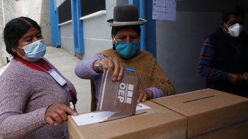 Una mujer aymara con una máscara en medio de la pandemia de coronavirus espera para emitir su voto en un colegio electoral durante las elecciones regionales en El Palomar, Bolivia, el domingo 7 de marzo de 2021.