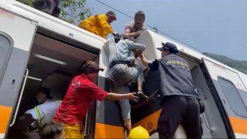 En esta imagen tomada de un video publicado por hsnews.com.tw, un pasajero (centro) recibe ayuda para subir encima de un tren descarrilado en la región de Hualien, en el este de Taiwán, el 2 de abril de 2021.